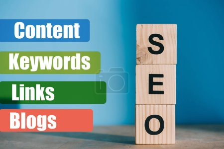 SEO word made from wooden blocks on blue background with Content, Keywords, Links, Blogs signs