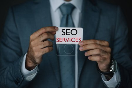 cropped view of developer in suit holding business card with SEO services