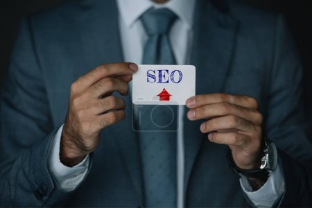 cropped view of professional developer in suit holding business card with SEO sign