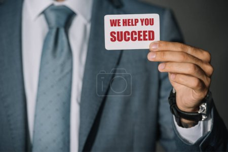 "partial view of businessman showing card with ""we help you succeed"" lettering"