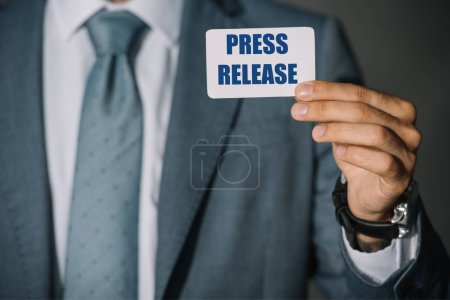 "partial view of businessman showing card with ""press release"""