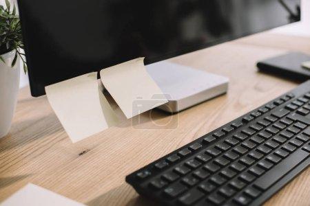 Photo pour Plan rapproché de l'écran d'ordinateur avec autocollants vierges et clavier sur le lieu de travail moderne - image libre de droit