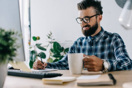 successful smiling seo with cup of coffee and computer writing notes at workplace