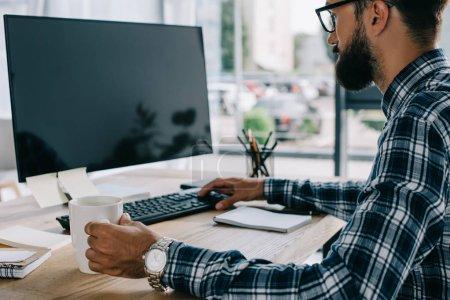Photo pour Jeune développeur efficace, assis au milieu de travail avec écran blanc - image libre de droit