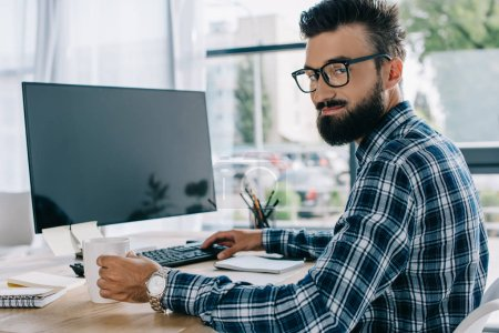 young successful seo sitting at workplace with blank computer screen and looking at camera