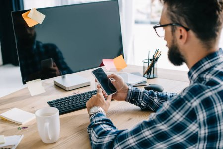 handsome young businessman using smartphone with blank screen at workplace