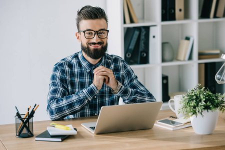 bearded smiling businessman in eyeglasses looking at camera while sitting at workplace with laptop