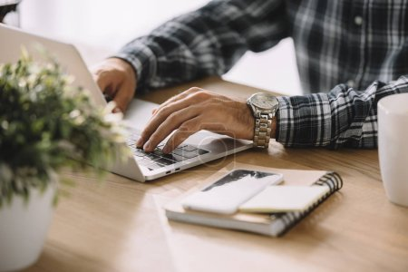 cropped shot of man in plaid shirt using laptop at workplace