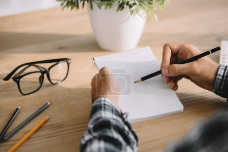 cropped shot of man writing in notebook at workplace