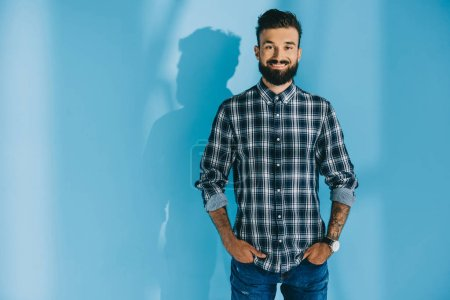 bearded smiling man in checkered shirt standing with hands in pockets, on blue