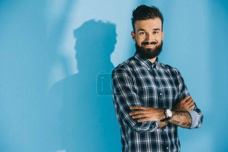 Photo pour Homme souriant barbu posant avec les bras croisés et regardant la caméra, sur bleu - image libre de droit