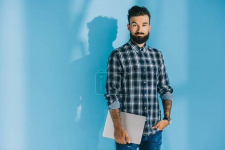 Photo for Bearded man in checkered shirt holding laptop, on blue - Royalty Free Image