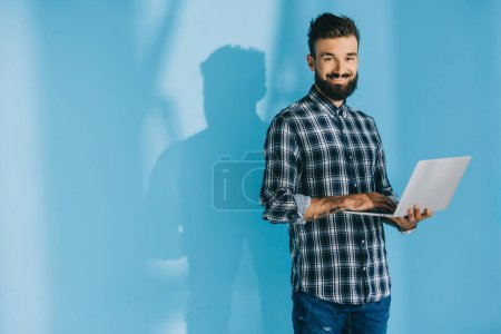 Photo for Handsome smiling man in checkered shirt using laptop, on blue - Royalty Free Image