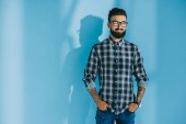 handsome bearded man in checkered shirt standing with hands in pockets, on blue
