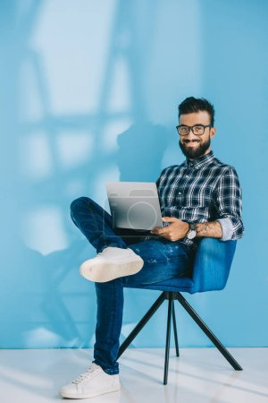 Photo for Smiling man using laptop and sitting in armchair, on blue - Royalty Free Image