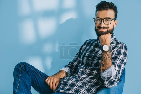 handsome bearded man in checkered shirt, on blue