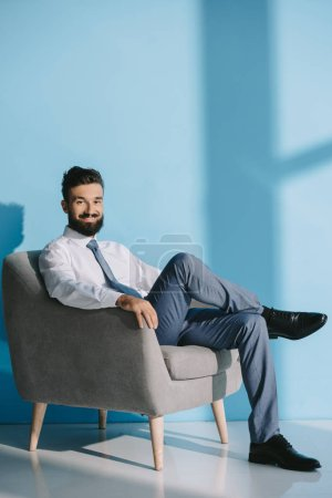 Photo for Smiling businessman in formal wear sitting in grey armchair, on blue - Royalty Free Image