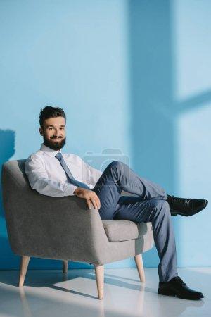 smiling businessman in formal wear sitting in grey armchair, on blue