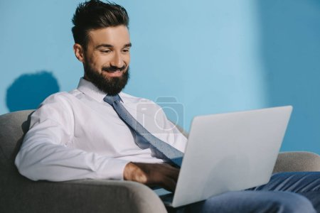 handsome smiling businessman using laptop and sitting in armchair, on blue