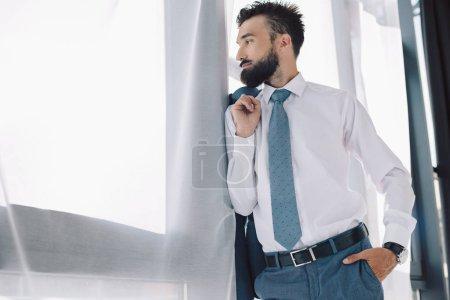 Photo pour Homme d'affaires barbu regardant fenêtre au bureau - image libre de droit