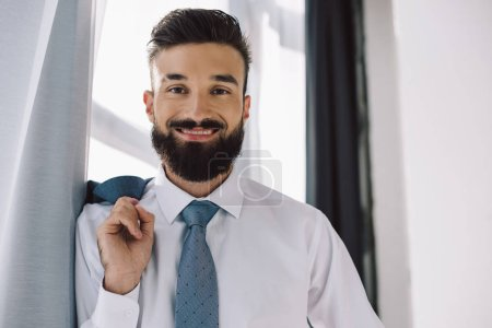 portrait of smiling businessman standing near window in office