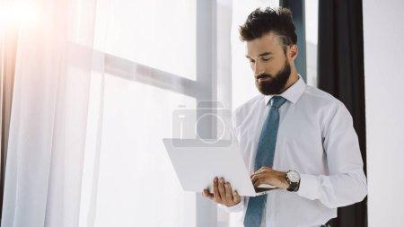 handsome bearded businessman using laptop near window in office