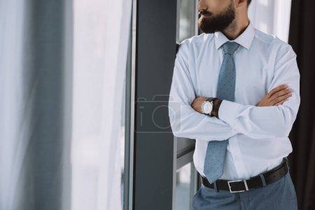 cropped view of businessman with crossed arms standing near window in office