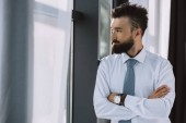 bearded businessman with crossed arms looking at window in office