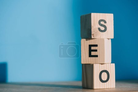 SEO word made from wooden alphabet cubes on blue background