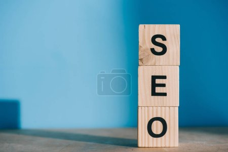 SEO word made from wooden blocks on blue background