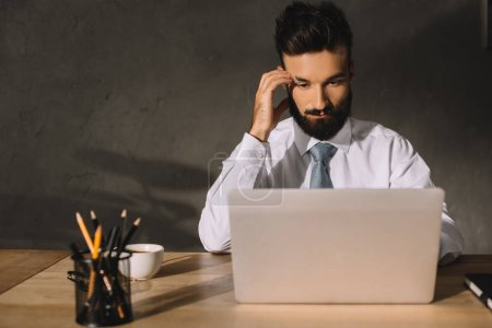 thoughtful businessman using laptop at workplace with coffee and pencils