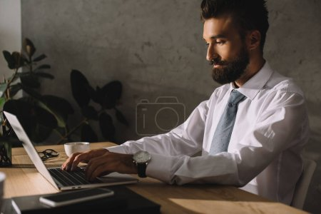 Photo for Handsome bearded businessman using laptop in office - Royalty Free Image