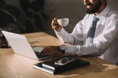 cropped view of businessman using laptop and holding cup of coffee at workplace