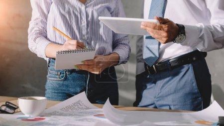 Photo pour Recadrée vue des collègues qui travaillent avec des documents et tablette numérique - image libre de droit