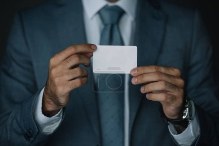 cropped view of businessman in suit holding business card in hands