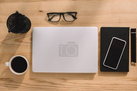 top view of office supplies, laptop, smartphone, eyeglasses and coffee cup