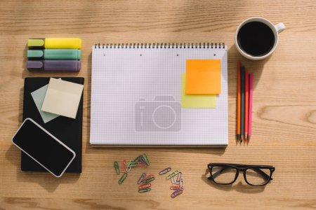 top view of office supplies, stick notes, smartphone, paper clips, notebook and cup of coffee