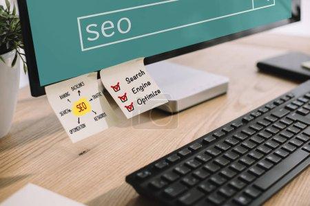 Photo pour Plan rapproché de l'écran d'ordinateur avec autocollants SEO et clavier sur le lieu de travail moderne - image libre de droit