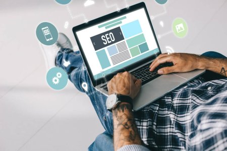cropped view of tattooed developer working on laptop with SEO icons