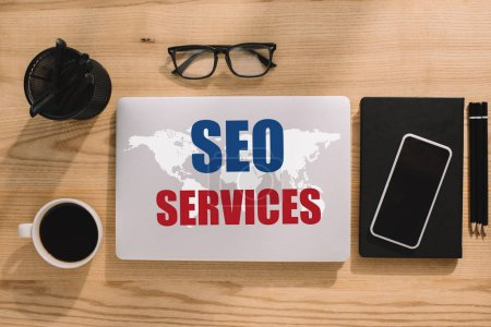 top view of SEO services and world map on laptop with office supplies around