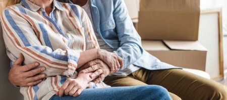 Photo for Partial view of senior couple holding hands and sitting together on couch in new house - Royalty Free Image