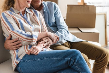 cropped shot of happy senior couple holding hands and sitting together on couch in new house