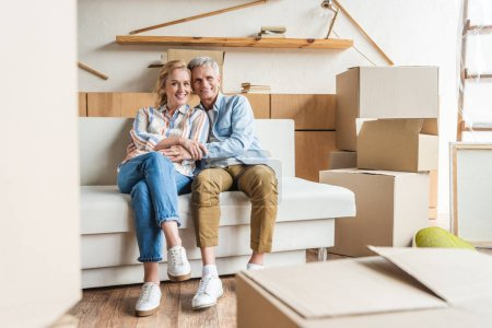happy elderly couple embracing and smiling at camera while sitting together on couch in new house