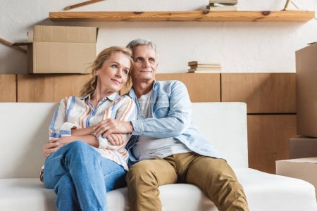 happy elderly couple embracing and sitting together on couch in new house