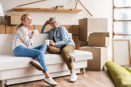 happy elderly couple holding cups and sitting on couch in new home
