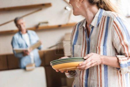 Foto de Recortar foto de mujer madura sosteniendo las placas y mirando el marido durante la relocalización - Imagen libre de derechos