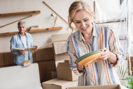 Photo for Smiling woman packing plates while husband with books standing behind during relocation - Royalty Free Image