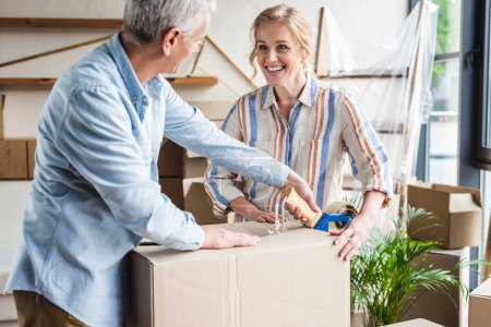Photo for Happy senior couple packing cardboard box and smiling each other during relocation - Royalty Free Image