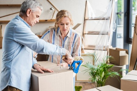 Photo for Focused senior couple packing cardboard boxes while moving home - Royalty Free Image