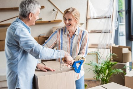 Photo for Happy elderly couple packing cardboard boxes during relocation - Royalty Free Image